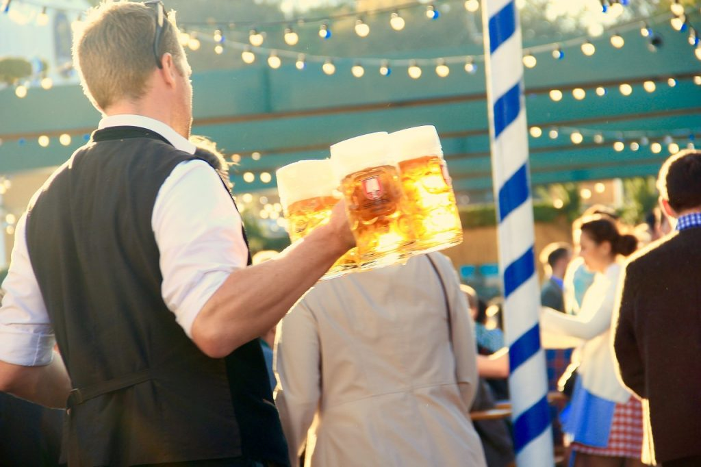 A man holder three large beer steins in an outdoor setting.